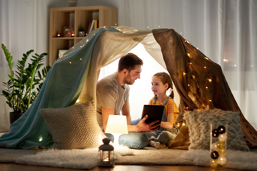 Blog - Happy Father and Daughter with Tablet in Child Play Tent at Night Inside the Home