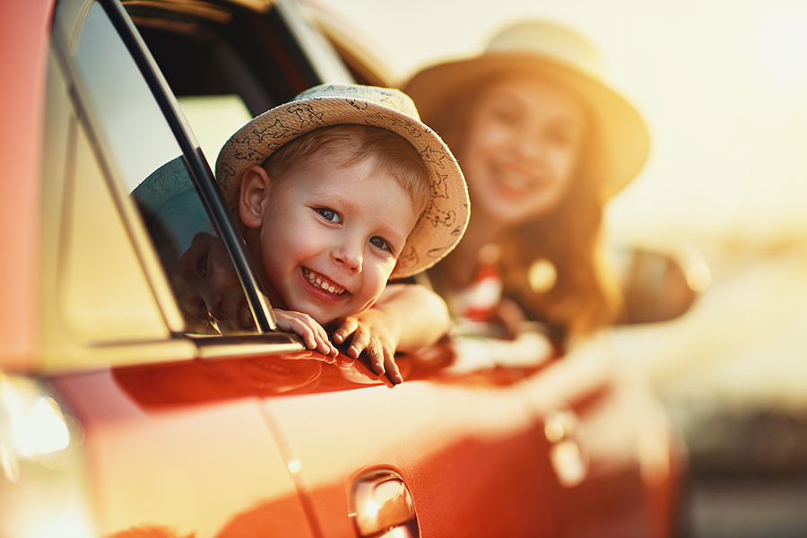 Personal Insurance - Happy Family of Mother and Child Boy Going on a Summer Trip in the Car