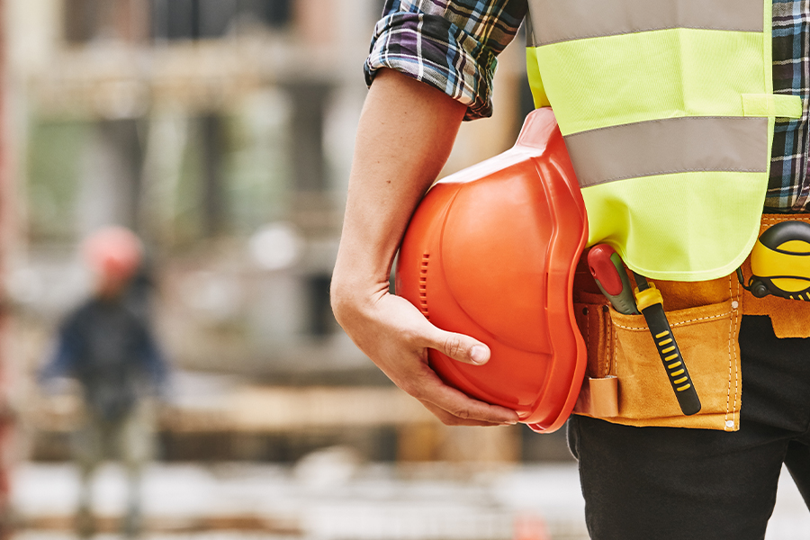 Specialized Business Insurance - Construction worker with Construction Tools Holding a Safety Helmet while Standing Outside at a Construction Site Blurred in the Background